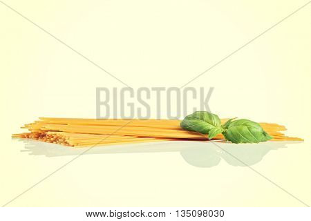 Uncooked dry fettuccine pasta  with green basil
