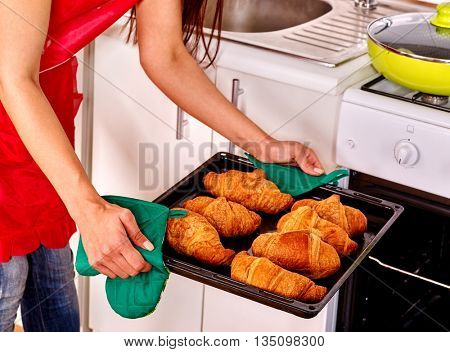 Young woman bake cookies on home kitchen. There are cookies on tray.