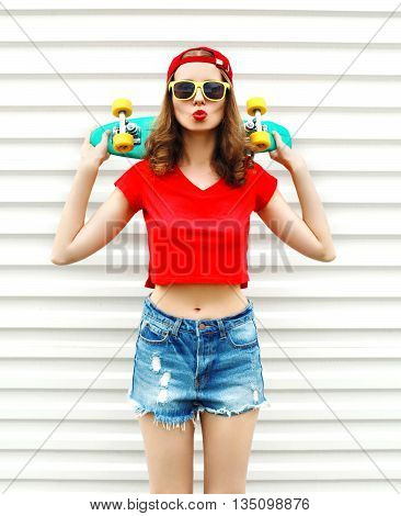 Fashion pretty cool woman in sunglasses and shorts with skateboard over white background