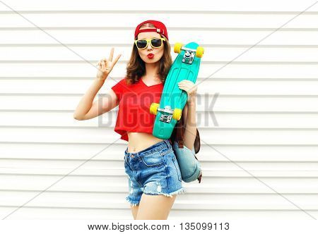 Fashion pretty cool woman with skateboard in sunglasses and shorts over white background
