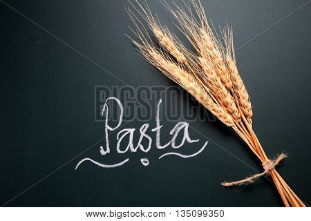 text pasta and wheat straw on the blackboard