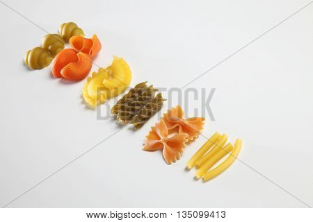 various raw pasta on the white background