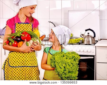 Children little girl cooking vegetable on their own at kitchen. Children keeps vegetable are kitchen.