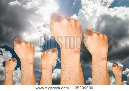 Human hand showing fist ready for fighting on dark tone sky background with flare on the sun