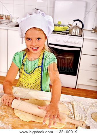Child girl wearing cooking hat cooking knead dough at kitchen.