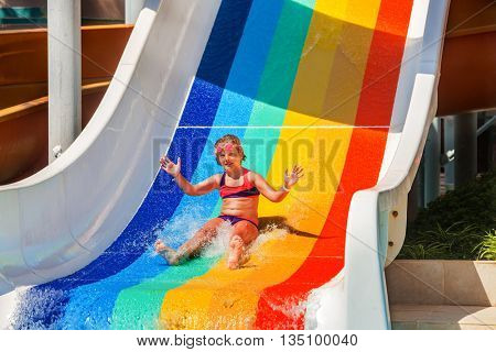 Child girl 8 years slide down the water slide at aquapark . Different colors painted children's slide. Summer water park holiday. Outdoor.