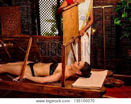 White seminude woman lie in sauna. Indian Ayurvedic sauna treatment. Indian woman sauna door closes.