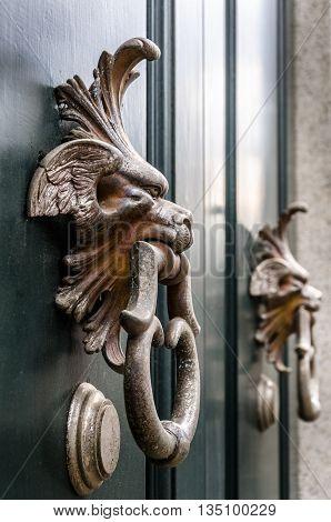 View on the door handle antique doors, Milan, Italy
