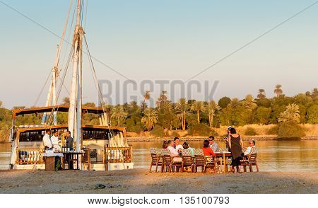 ASWAN EGYPT - NOVEMBER 30 2011: Tour party having evening drinks on banks of the Nile.