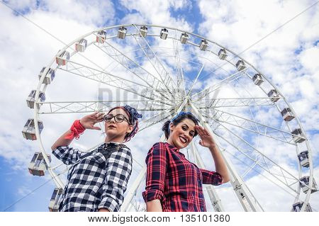Two friends posing in camera with ferris wheel in background - Girls dressed in pin up 50's style - Fashion lifestyle concept - Warm filter tihe soft vignette editing - Soft focus on faces