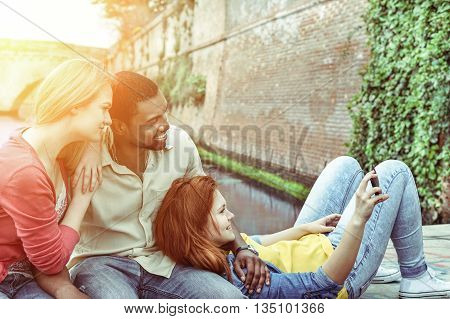 Multicultural friends watching cell phone screen during summer time outdoor - Cheerful multiracial people taking selfie sitting next river - New technology addiction concept - Soft focus on right girl