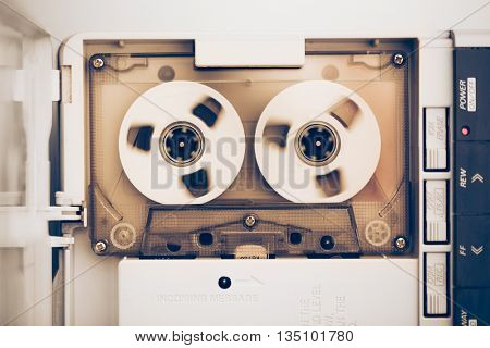rewinding of vintage audio tape compact cassette, sepia tone