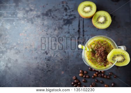 Green smoothie of kiwi sprinkled with chocolate healthy cocktail with straw on dark metal rusty table copy space at left