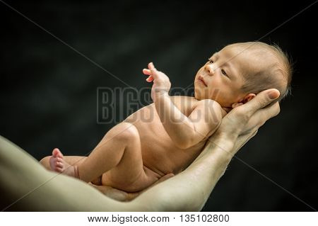 Infant Resting On His Father's Hand