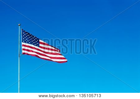 USA flag flies in a wind on blue sky background place for your text