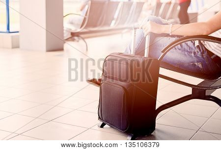Woman waiting for her flight at airport and holding her luggage