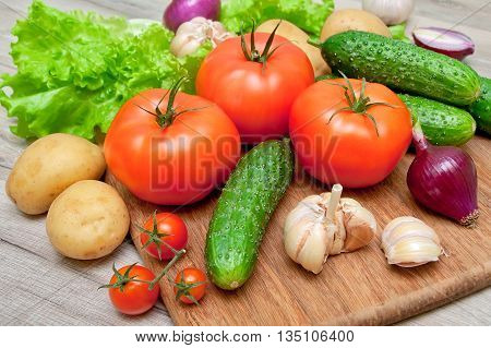 ripe tomatoes and other vegetables on a cutting board. horizontal photo.
