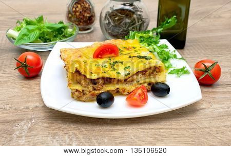 Appetizing lasagna with tomato and olives on a plate. horizontal photo.