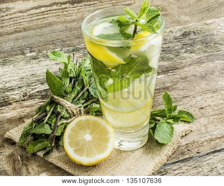 detox water with lemon and mint in a glass on a background of leaves of mint and strawberries on a wooden table close-up