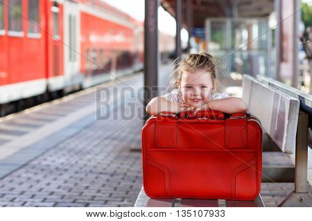 Cute little girl with big red suitcase on a railway station. Kid waiting for train and happy about a journey.