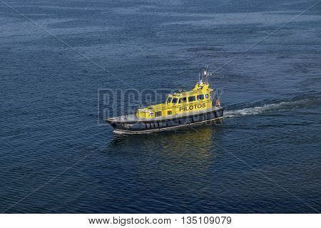 PORT OF LEIXOES PORTUGAL - 13 JULY 2015 - The colorful yellow pilot boat from the Port of Leixoes Porto speeds off after having safely guided a cruise ship into open waters