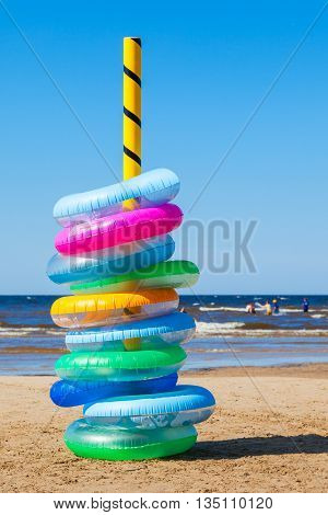 Stack of colorful inflatable swimming rings on sea beach