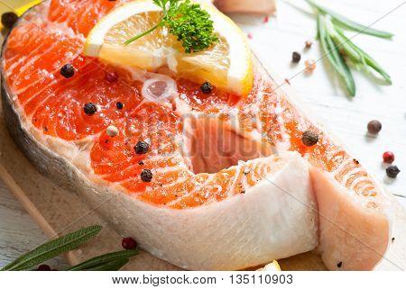 Fresh fish. Salmon. Raw salmon steak with sea salt pepper and herbs. Food background.