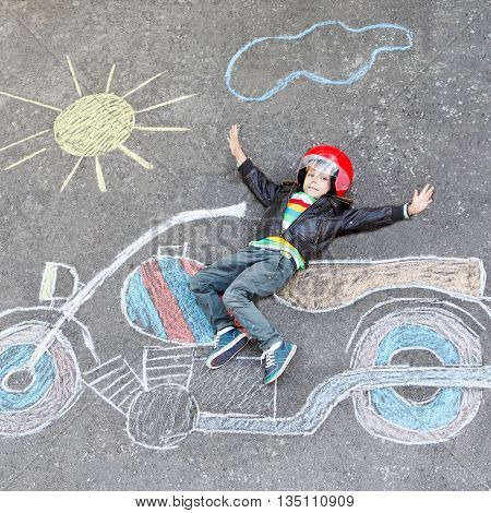 Creative leisure for children: Happy little child of four years in helmet having fun with motorcycle picture drawing with colorful chalks. Children, lifestyle, fun concept.