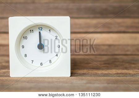 Closeup white clock showed twelve o'clock on blurred brown wood board background
