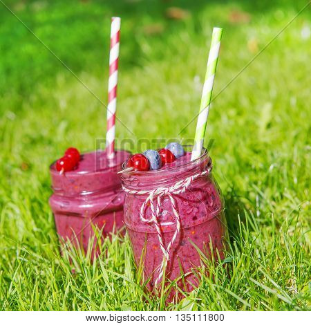 Fresh smoothie drink with different berries as healthy breakfast. On green grass background