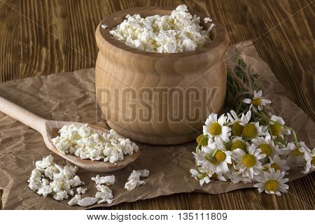 Cottage cheese and chamomile flowers on wooden background