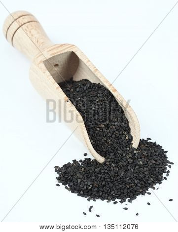 Organic peeled black sesame seeds. Black sesame seeds in wooden spoon. Sesame seeds on white background.