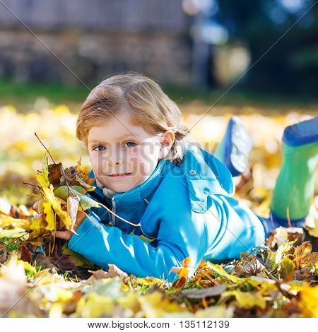 Cute kid boy laying with a lot of yellow autumn leaves in park. Kid boy having fun on sunny warm october day. Season, children, lifestyle concept