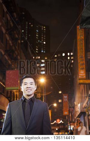 Asian businessman in chinatown at night