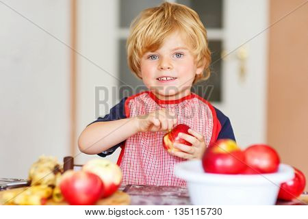 Adorable little kid boy having fun with making backed apples domestic kitchen, indoor. Child filling apples with marzipan