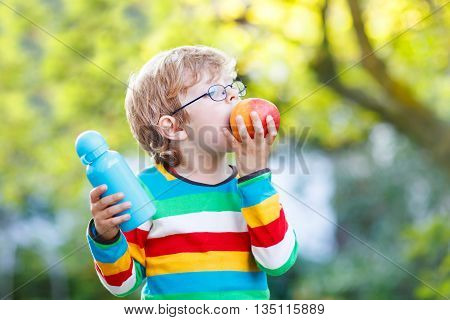 Happy little boy with books, apple and drink bottle on his first day to elementary school or nursery. Outdoors.  Back to school, kids, lifestyle concept. Child eating fruit