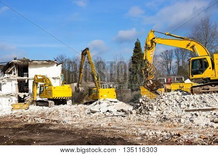 Three yellow demolition cranes dismantling a building