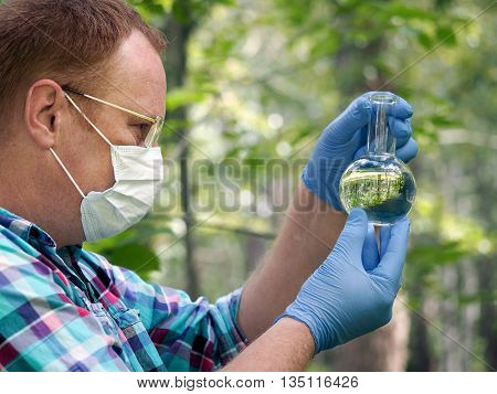 A man wearing glasses mask and gloves holding a retort with a transparent liquid. Concept - the study of water quality chemical analysis environment ecology
