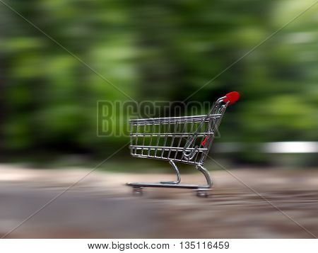 Grocery supermarket trolley in the forest. The trolley is empty rushing at high speed. Concept - eco-friendly products to buy quickly