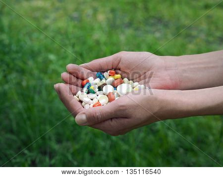 Female hands holding a handful of multi-colored pills. Natural background - green grass