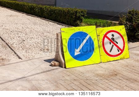 Road signs at the under construction sidewalk in summer day