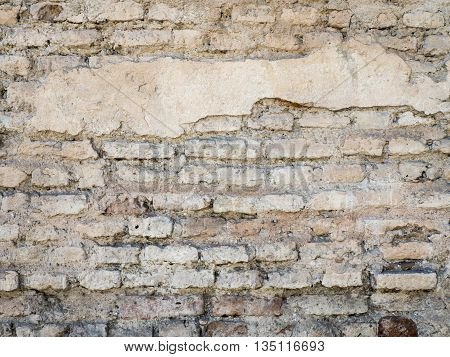 Old damaged rustic brick wall with plaster texture background. Close up.