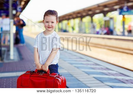 Cute little kid girl walking alone with big red suitcase on a railway station. child waiting for train and happy about a journey. People, travel, lifestyle concept