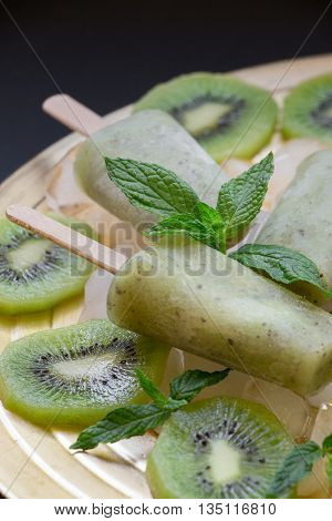 Kiwi sorbet ice cream popsicles on golden plate with ice cubes chopped kiwi slices and mint leaves on a black background. Kiwi sorbet ice cream popsicles. Vertical. Close.