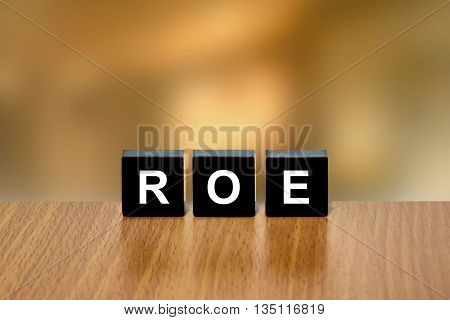 ROE or return on equity on black block with blurred background