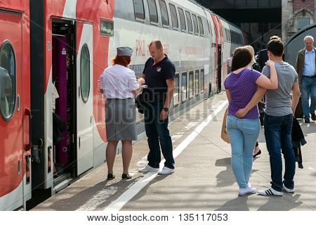 Moscow Russia - June 14.2016. The conductor checks the tickets and documents when boarding the train