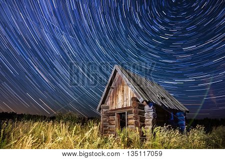 Cabin in the night forest. Star trail.