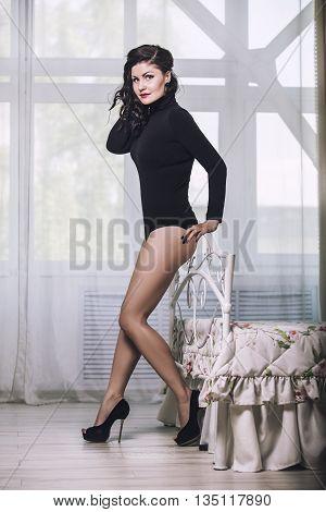 Beautiful Brunette Woman Model In A Black Bodysuit Lingerie In The Bedroom