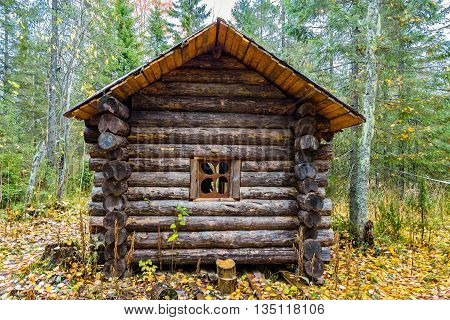 Little old Russian log hut in a forest in autumn