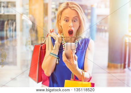 Shocked woman at the shopping mall looking at her smartphone